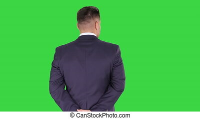 Businessman walking and looking around holding hands behind his back on a Green Screen, Chroma Key.