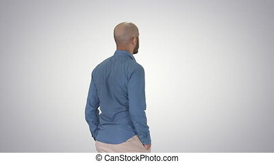 Casual young man walking on gradient background. - Medium...