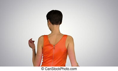 Medium shot. Back view. Girl Dancing in Orange SunDress on gradient background. Professional shot in 4K resolution. 023. You can use it e.g. in your commercial video, business, presentation, broadcast