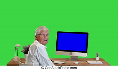 Medium shot. Back view. Old businessman sitting at the table with blank screen pc and talking to camera Mock-up Display on a Green Screen, Chroma Key. Professional shot in 4K resolution. 064. You can use it e.g. in your medical, commercial video, business, presentation, broadcast