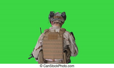 Medium shot. Back view. Ranger in combat uniform walking on a Green Screen, Chroma Key. Professional shot in 4K resolution. 048. You can use it e.g. in your medical, commercial video, business, presentation, broadcast