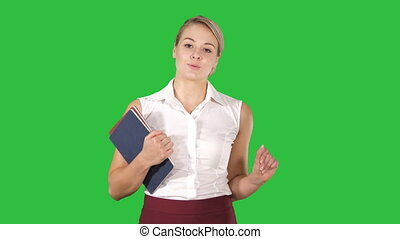 Beautiful teacher with notebooks explaining something to camera on a Green Screen, Chroma Key.
