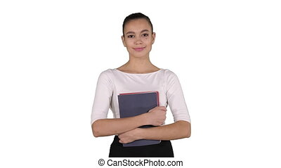 Beautiful young woman with notebooks walking on white background.