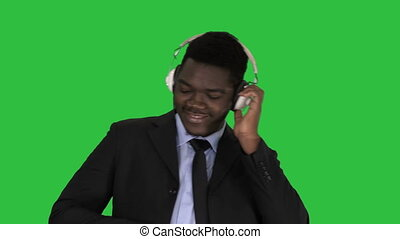 Black businessman dancing to music in headphones on a Green Screen, Chroma Key.