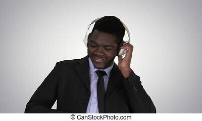 Black businessman dancing to music in headphones on gradient background.