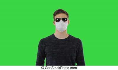 Medium shot. Blind man in face mask and in dark glasses with walking on a Green Screen, Chroma Key. Professional shot in 4K resolution. 53. You can use it e.g. in your medical, commercial video, business, presentation, broadcast