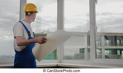 Builder at construction site with blueprint.