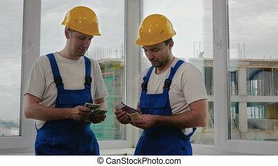 Builders in helmets counting salary.