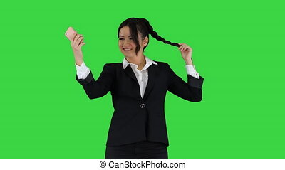 Business woman look into smart phone preening and dancing on...