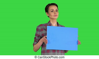Casual woman with short hair with blue blank board mock up on a Green Screen, Chroma Key.