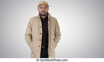 Confident man in trench holding hands in the pockets and walking on gradient background.