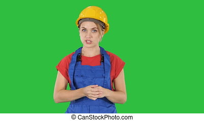 Construction female worket explaining her ideas to camera on a Green Screen, Chroma Key.