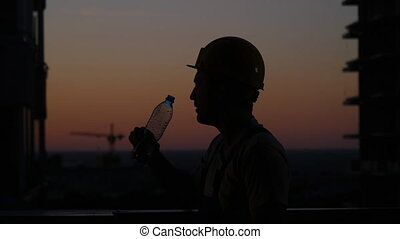Construction Man Drink Water in a Hot Summer Day.