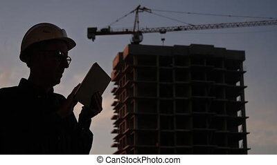 Construction manager using tablet on building site.