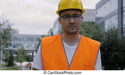 Construction worker in hard hat and glasses walking. - ...
