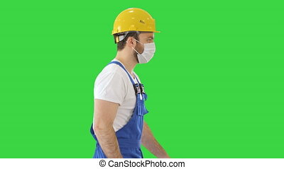 Medium shot. Construction worker wearing a hardhat and mask walking on a Green Screen, Chroma Key. Professional shot in 4K resolution. 53. You can use it e.g. in your medical, commercial video, business, presentation, broadcast