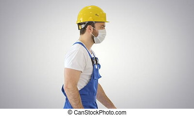 Construction worker wearing a hardhat and mask walking on gradient background.