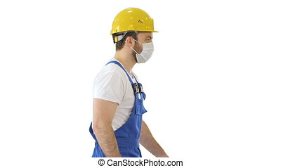 Construction worker wearing a hardhat and mask walking on white background.