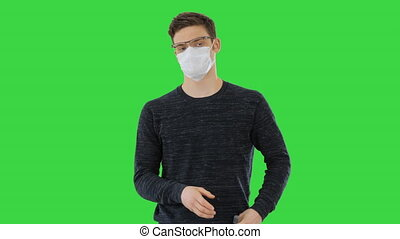 Coronavirus Man wearing protective mask cleaning his hands with sanitizer on a Green Screen, Chroma Key.