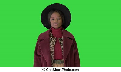 Medium shot. Cute afro model in coat touching hat walking on a Green Screen, Chroma Key. Professional shot in 4K resolution. 4151. You can use it e.g. in your commercial video, business, presentation, broadcast