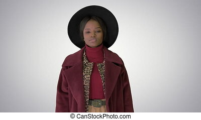 Medium shot. Cute afro model in coat touching hat walking on gradient background. Professional shot in 4K resolution. 4151. You can use it e.g. in your commercial video, business, presentation, broadcast