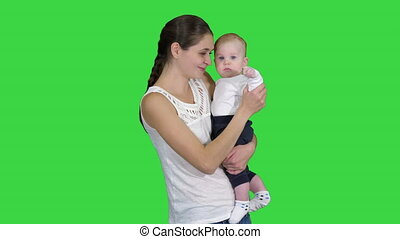 Cute baby boy in mothers hands looking to camera on a Green Screen, Chroma Key.