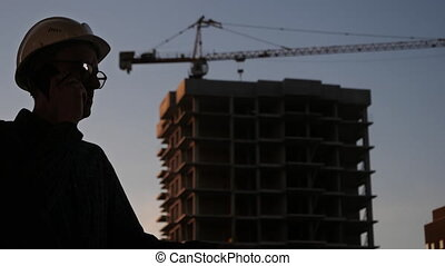 Engineer in a white hard hat talking on the phone. ...