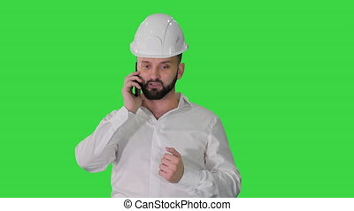 Engineer in white shirt and hard hat talking on his mobile ...