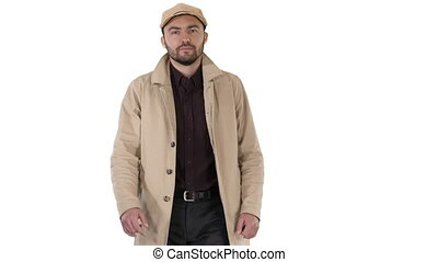 Fashionable man with dark beard in trench coat walking on...