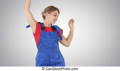 Female construction worker dancing with hardhat on gradient...