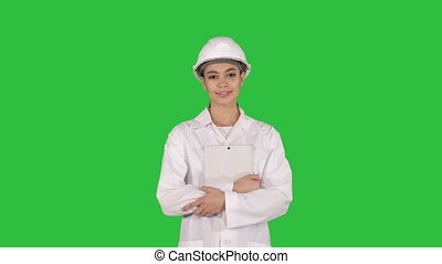 Female doctor engineer walking with digital tablet on a Green Screen, Chroma Key.