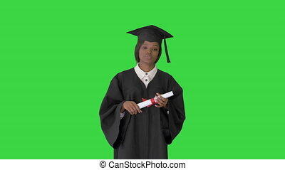 Medium shot. Front view. African American female graduate holding diploma and giving speech on a Green Screen, Chroma Key. Professional shot in 4K resolution. 046. You can use it e.g. in your medical, commercial video, business, presentation, broadcast