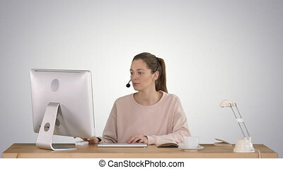 Beautiful young casual woman wearing headset working on computer on gradient background.