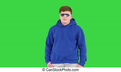 Medium shot. Front view. Boy kid wearing casual clothes and cool sunglasses standing doing nothing on a Green Screen, Chroma Key. Professional shot in 4K resolution. 062. You can use it e.g. in your medical, commercial video, business, presentation, broadcast