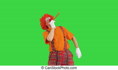 Medium shot. Front view. Clown with red nose blowing party horn on a Green Screen, Chroma Key. Professional shot in 4K resolution. 061. You can use it e.g. in your medical, commercial video, business, presentation, broadcast