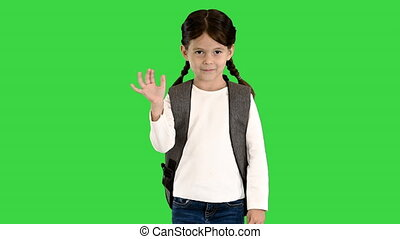 Medium shot. Front view. Cute little schoolgirl with backpack waving to the camera on a Green Screen, Chroma Key. Professional shot in 4K resolution. 060. You can use it e.g. in your medical, commercial video, business, presentation, broadcast