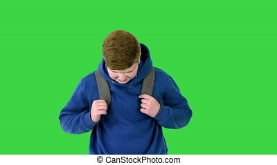 Medium shot. Front view. Cute schoolboy with backpack walking carefully on a Green Screen, Chroma Key. Professional shot in 4K resolution. 062. You can use it e.g. in your medical, commercial video, business, presentation, broadcast