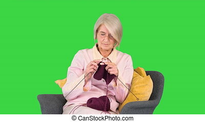 Medium shot. Front view. Elderly woman knitting woolen clothes on a Green Screen, Chroma Key. Professional shot in 4K resolution. 063. You can use it e.g. in your medical, commercial video, business, presentation, broadcast