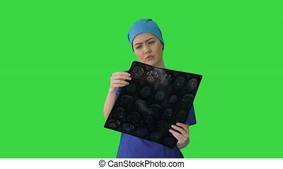 Female doctor looking at brain tomography on a Green Screen, Chroma Key.