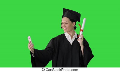 Medium shot. Front view. Happy female graduate holding diploma and making selfie on her phone on a Green Screen, Chroma Key. Professional shot in 4K resolution. 043. You can use it e.g. in your medical, commercial video, business, presentation, broadcast