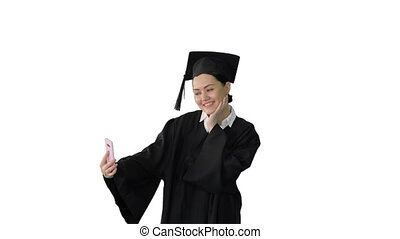 Medium shot. Front view. Happy female graduate in mortarboard making selfie on her phone on white background. Professional shot in 4K resolution. 043. You can use it e.g. in your medical, commercial video, business, presentation, broadcast