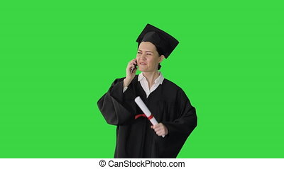 Medium shot. Front view. Happy female student in graduation robe talking emotionally on the phone while walking with diploma on a Green Screen, Chroma Key. Professional shot in 4K resolution. 043. You can use it e.g. in your medical, commercial video, business, presentation, broadcast