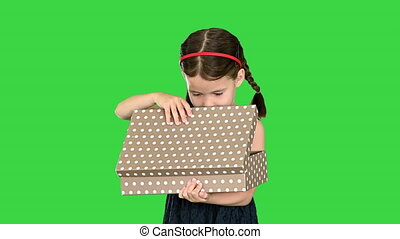 Happy girl in black dress shaking and opening gift box smiling at camera on a Green Screen, Chroma Key.