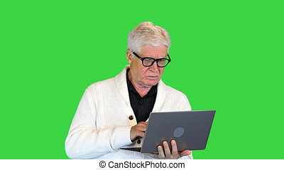 Medium shot. Front view. Happy senior holding a laptop and typing on a Green Screen, Chroma Key. Professional shot in 4K resolution. 064. You can use it e.g. in your medical, commercial video, business, presentation, broadcast