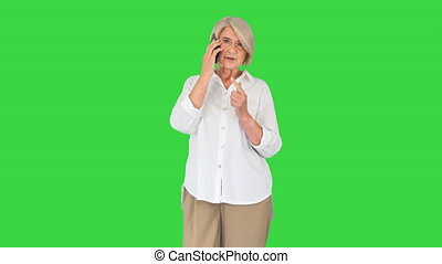 Medium shot. Front view. Happy senior woman with smartphone making a call on a Green Screen, Chroma Key. Professional shot in 4K resolution. 063. You can use it e.g. in your medical, commercial video, business, presentation, broadcast