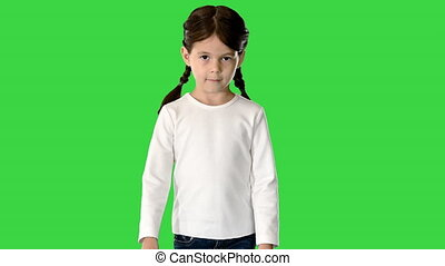 Medium shot. Front view. Little girl with pig tails dressed in white long sleeve top and jeans walking and looking at camera on a Green Screen, Chroma Key. Professional shot in 4K resolution. 060. You can use it e.g. in your medical, commercial video, business, presentation, broadcast