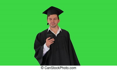 Male student in graduation gown checking his phone while walking on a Green Screen, Chroma Key.