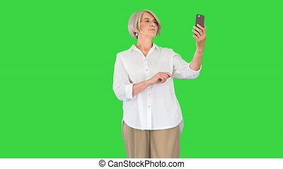 Positive elderly woman smiling and using her smartphone while making selfies on a Green Screen, Chroma Key.