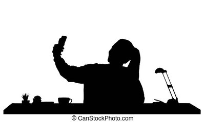 Silhouette Beautiful woman taking a selfie with her cell phone sitting at the desk.