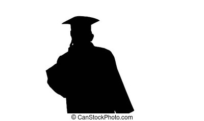 Silhouette Male graduate in gown and mortarboard talking on ...